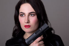 Close up portrait of beautiful woman with gun over grey Royalty Free Stock Photos