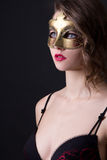 Close up portrait of beautiful woman in lingerie and mask over g Stock Images