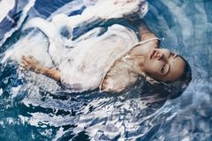Close up portrait of beautiful woman lying in water with fabric. royalty free stock photo