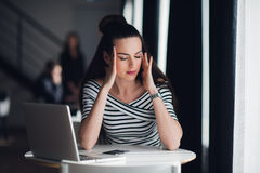 Close up portrait of beautiful woman meditating with closed eyes. Attractive female relaxing from working with a laptop. Royalty Free Stock Image