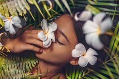 Close up portrait of beautiful woman with frangipani flowers royalty free stock photo