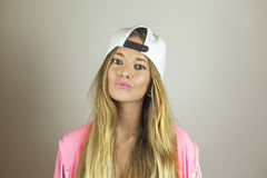 Close up portrait beautiful woman with pink sweatshirt and white. Cap shoot in studio, isolated on a white background Royalty Free Stock Photos