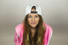 Close up portrait beautiful woman with pink sweatshirt and white. Cap shoot in studio, isolated on a white background Royalty Free Stock Photo
