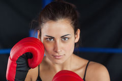 Close up portrait of a beautiful woman in red boxing gloves Royalty Free Stock Images