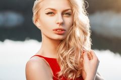 Close-up portrait of a beautiful woman with red dress on the bac. Kground of the sea. Sunset light Royalty Free Stock Photos
