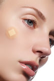 Close-up portrait of beautiful woman's purity face with natural make-up. Cute model with clean shiny skin. Beautiful young woman. With clear-up patches or Royalty Free Stock Photo