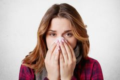 Close up portrait of beautiful woman sneezes and coughs, uses tissue, rubs nose, has bad cold,  over white background. Low. Spirited desperate woman suffers Stock Images