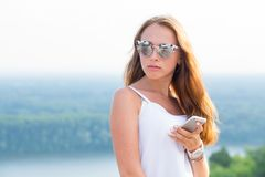 Close up portrait of a beautiful woman in sunglasses uses smartphone outdoors. stock photos