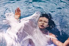 Close up portrait of beautiful woman under water with fabric. Fa royalty free stock image
