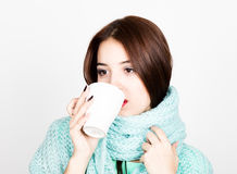 Close-up portrait of beautiful woman in a woolen scarf, drinking hot tea or coffee from white cup Stock Images