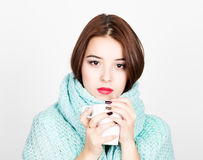 Close-up portrait of beautiful woman in a woolen scarf, drinking hot tea or coffee from white cup Royalty Free Stock Images