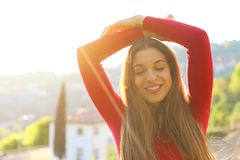 Close-up portrait of beautiful young adult woman in the sunlight at sunset. Pretty smiling girl. Beautiful woman is enjoying warm royalty free stock image