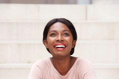 Close up beautiful young black woman laughing and looking up royalty free stock image