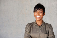 Close up beautiful young black woman smiling against gray wall Royalty Free Stock Photos