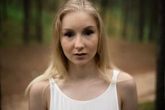 Close up portrait - Beautiful young blonde woman forest nymph in white dress in evergreen wood stock photo