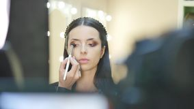 Close up portrait of beautiful young brunette woman applying eye-zone make up with cosmetic brush stock footage