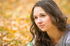 Close-up portrait of a beautiful young girl on the blurry background yellow foliage Stock Photos