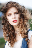 Close-up portrait of a beautiful young girl with curly brown hai Stock Image