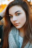 Close-up portrait of a beautiful young girl in a gray knitted sc royalty free stock photography