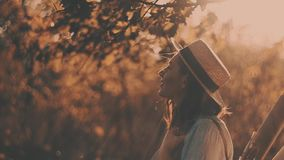 Close-up portrait of a beautiful young girl with long dark hair wearing straw hat. She plays with her hair in the warm. Rays of setting sun. Young girl in the stock footage