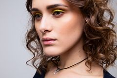 Close-up portrait of beautiful young girl with make-up and curly hair royalty free stock image