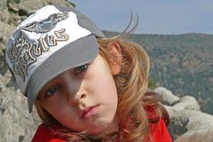 Close up portrait of a beautiful young girl. Portrait of a serious girl wearing big cap with sad eyes Royalty Free Stock Image