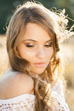 Close up portrait of a beautiful young lady model in field at sunset Royalty Free Stock Photography
