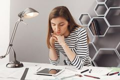 Close up portrait of beautiful young serious female architect student with brown hair in striped look, holding head with. Hands, looking in digital tablet with royalty free stock photography