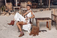 Close up portrait of beautiful young stylish boho woman sitting on wooden chair on the beach at sunset royalty free stock photos