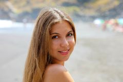 Close up portrait of beautiful young woman on the beach. Young female model on the sea shore royalty free stock photography