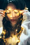 Close up portrait of a beautiful young woman with christmas ligh. Ts and closed eyes. Holiday concept Stock Images