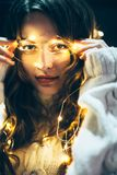 Close up portrait of a beautiful young woman with christmas ligh. Ts. Holiday concept Royalty Free Stock Image