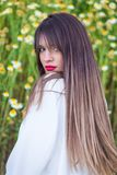 Close up portrait of beautiful young woman in front of some flow. Ers royalty free stock image