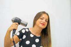 Close up portrait of a beautiful young woman with a hair dryer. Cute little girl smiles stock photo