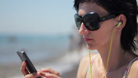 Close up portrait of beautiful young woman with headphones and sunglasses listening music on smartphone on sea stock video