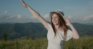 Close up portrait of beautiful young woman in nature with brunette hair blowing in wind looking at mountain view. Attractive Young woman having fun outside stock video footage
