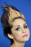 Close-up portrait of beautiful young woman with spiked hair over blue background Royalty Free Stock Photos