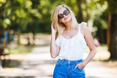 Close-up portrait of a beautiful young woman in sunglasses in a summer park. Optics style. Beauty, fashion outdoor Stock Photo