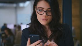 Close-up Portrait of Beautiful Young Woman Using Smartphone in Office. Business Lady in Formal Wear Dress Typing