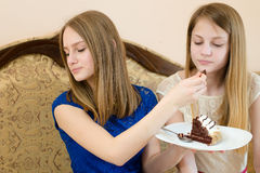 Close up portrait of 2 beautiful young women cute blond sisters or girls friends having fun eating cake. Diet & creamy chocolate cake: close up portrait of 2 Royalty Free Stock Images