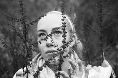 Close up portrait of beautiful youngwoman behind some red forest weeds. Close up black and white portrait of beautiful young blond woman behind some red forest Royalty Free Stock Photos