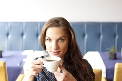 Beautifull young woman drinking cofee. Close up Portrait of beautifull blue eyed woman drinking cofee. Looking at camera Stock Image