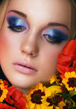 Close-up portrait of beauty young woman. With purple eyeshadows and pink lips with iris flowers Royalty Free Stock Photos