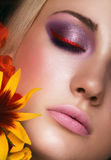 Close-up portrait of beauty young woman. With purple eyeshadows and pink lips with iris flowers Stock Image