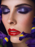 Close-up portrait of beauty young woman. With purple eyeshadows and red lips with iris flowers Stock Photo