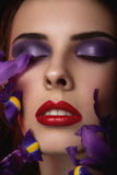 Close-up portrait of beauty young woman. With purple eyeshadows and red lips with iris flowers Stock Photos
