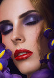 Close-up portrait of beauty young woman. With purple eyeshadows and red lips with iris flowers Stock Photography
