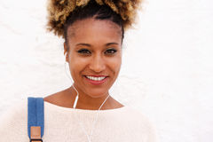 Close up black woman with earphone standing against white wall. Close up portrait of black woman with earphone standing against white wall Stock Photo