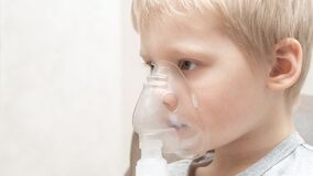 Close up portrait of blond boy taking inhalation for asthma prevention. Pale sick boy on a white background with a mask on his