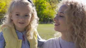 Close-up portrait of blond caucasian woman with curly hair holding little pretty girl on hands. Happy smiling mother and stock video footage